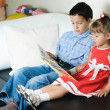 Stock Photo: Boy reading a book to his sister