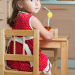A little girl at a table — Stock Photo