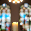 Church interior with candle and stained glass windows — Stock Photo