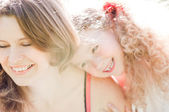 Happy little daughter hugging her young mother — Stock Photo