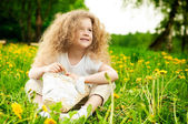 Little girl on flower field — Stock Photo