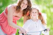 Genç anne ve kızı bisiklet üzerinde — Stok fotoğraf