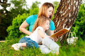 Mother reading book to her daughter — Stockfoto