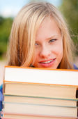 Young student girl with pile of books — Stock Photo