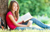 Happy young student girl with book — Stok fotoğraf