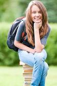 Happy student girl sitting on books — Stock Photo