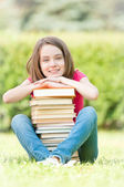 Student szczęśliwy dziewczyna siedzi w pobliżu stos książek — Zdjęcie stockowe