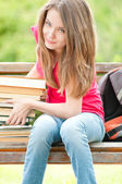 Happy student girl sitting on bench with pile of books — Stock Photo