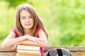 Happy student girl sitting on bench with books and smiling — Stock Photo
