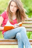 Garota estudante sério sentado no banco com livro — Foto Stock
