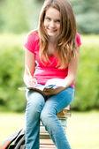 Genç öğrenci kız kitap yığınının üzerinde oturuyordu — Stok fotoğraf