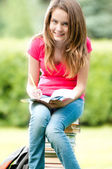 Young student girl sitting on pile of books — Stock Photo