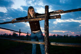 Girl standing near farm fence — Stock Photo