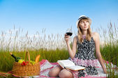Young girl reading book and drinking wine — Stock Photo