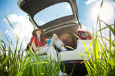 Young woman resting in car — Stockfoto