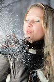 Flickan med snö i hennes händer — Stockfoto