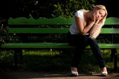 Sad young woman sitting on bench in park — Stock Photo