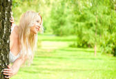 Woman looking out from behind the tree — Stock Photo