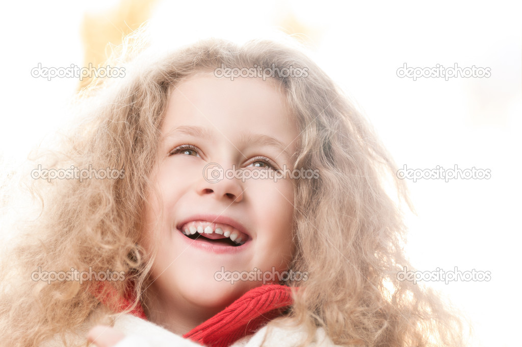Beautiful little girl laughing in autumn park. Strong backlight.  Stock Photo #11431148
