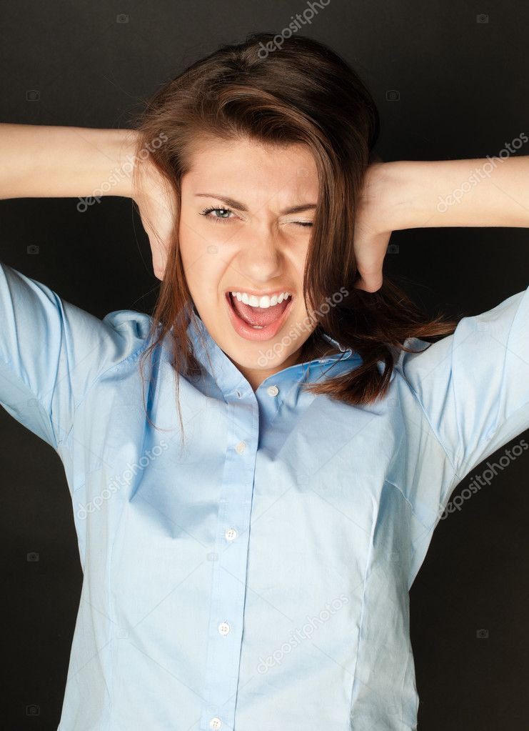 Beautiful young woman in blue shirt with dark hair screaming. Hands at her ears, mouth wide open, looking into the camera, dark background. — Stock Photo #11436362