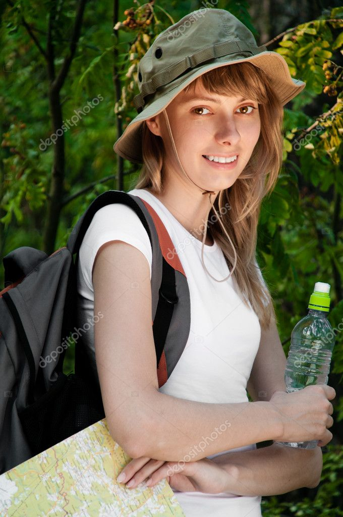 Beautiful young woman standing in forest with backpack, map and bottle of water, smiling and looking in camera — Stock Photo #11436705