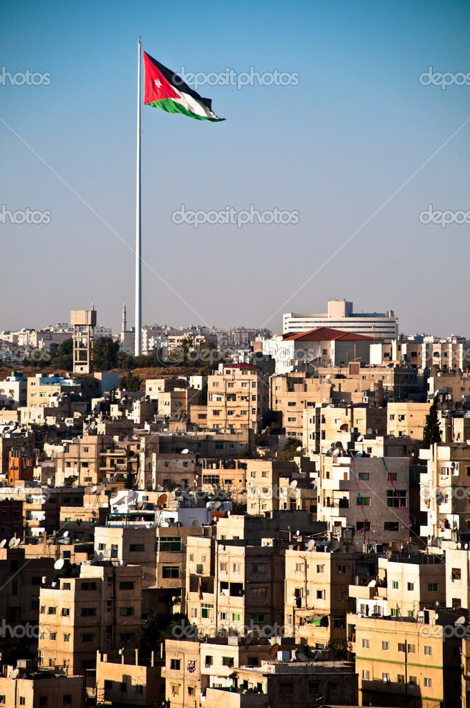 View of city of Amman with giant jordanian flag and blue sky in background — Stock Photo #11438959