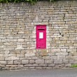 Red postbox in a wall — Stock Photo