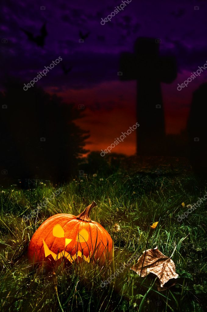 Halloween jack o lantern in cemetery with cross in background — Stock Photo #11466247