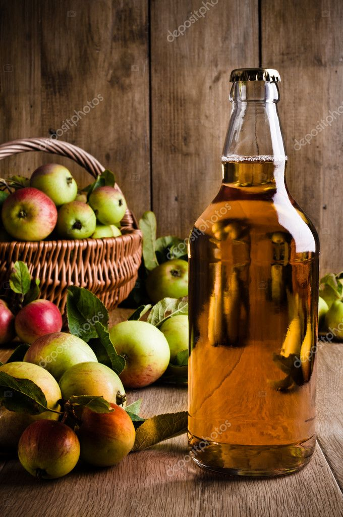 Full bottle of cider with basket of apples — Stock Photo #11467140