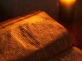 Biblia w światło świeca — Zdjęcie stockowe