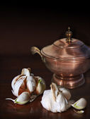 Garlic cloves and an old copper cask in chiaroscuro — Stock Photo