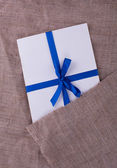 The envelope tied with a blue ribbon on sacking — Stock Photo
