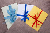 Three envelope sacking tied with ribbon — Stock Photo