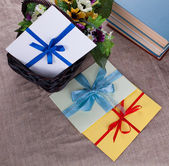 Three envelope and three books against the basket and sacking — Stock Photo
