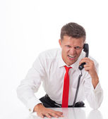 Angry businessman sitting at his desk and screaming — Stock Photo