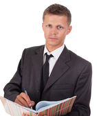 Businessman writes something in a book and looking at the camera — Stock Photo
