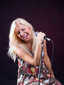 The girl singing into a microphone emotionally — Stock Photo