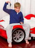 Boy and his supercar bed with keys — Stock Photo