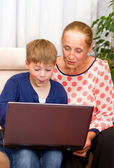 Cute grandson and grandmother looking at laptop — Stock Photo