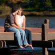 Stock Photo: Young Couple In Love Sits Barefoot On Dock