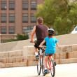 Stock Photo: MAnd Child Ride Tandem Bike In City