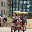 Stock Photo: Tourist Family Pedals Four Wheeled Bike Along Lake Shore Drive