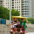 Stock Photo: Tourists Pedal Four Wheeled Cycle Along Chicago Asphalt