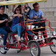 Young Adults Pedal A Four-Wheeled Cycle Along Lakeshore Drive - Photo
