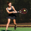 Stock Photo: Female Tennis Player Hits Powerful Backhand Shot