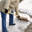 Stock Photo: Woman is shovelling snow