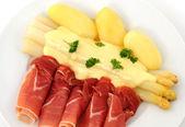 Main course of white asparagus, sauce hollandaise, potatoes and Serrano ham — Stock Photo