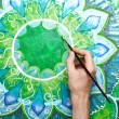 Man painting bright green picture with circle pattern, mandala o — Stock Photo #11567762