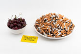 Cherries and cigarettes — Stock Photo