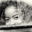 Little girl from Madagascar smiles behind the window — Lizenzfreies Foto